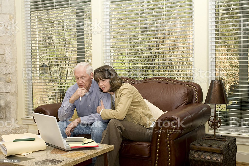 Senior adult couple studying the laptop computer results. Investments, bills. royalty-free stock photo