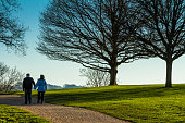 Senior Adult Couple walking on countryside path holding hands