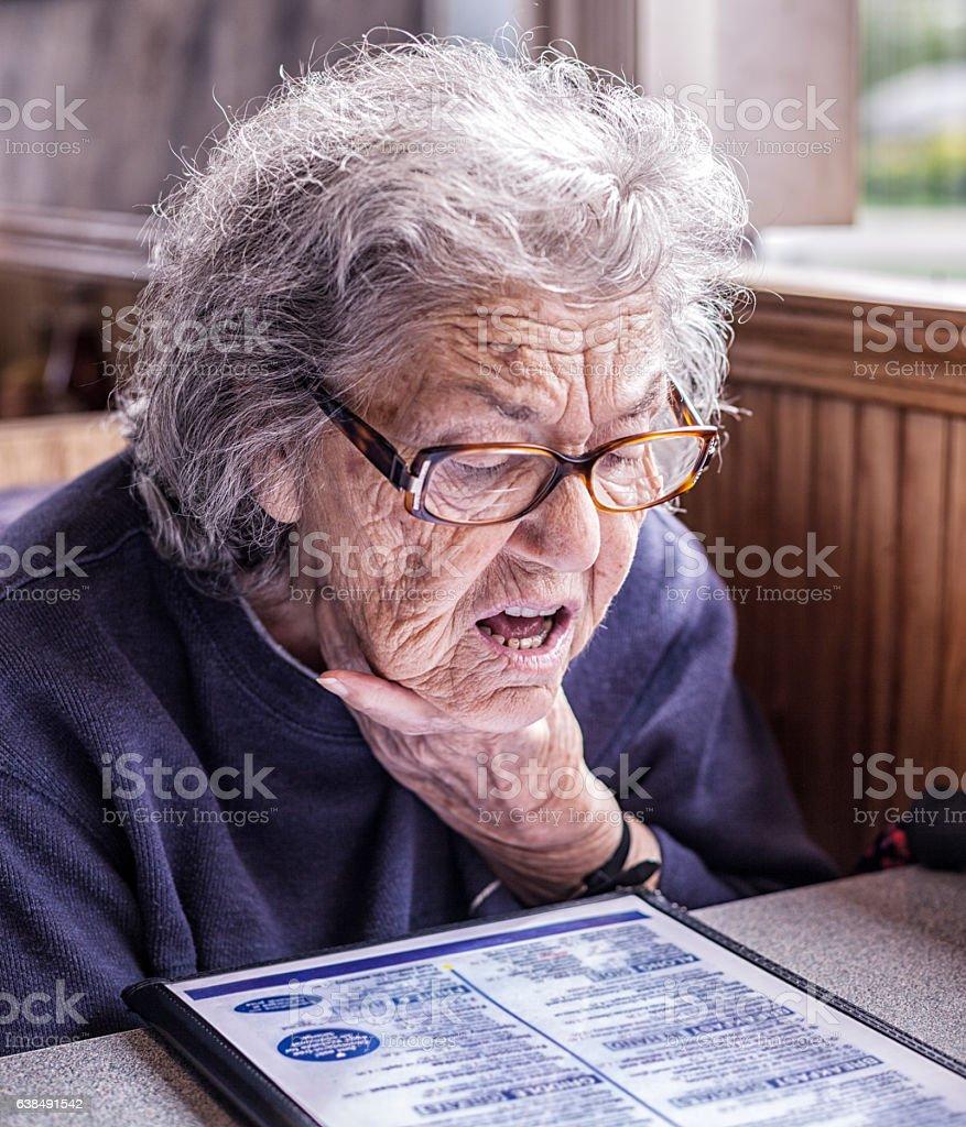 Senior Adult Dementia Woman Reading Restaurant Breakfast Menu stock photo