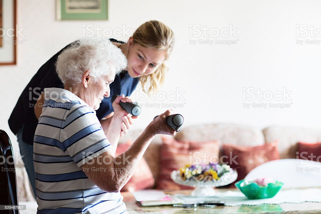 senior adult doing physiotherapy supported by therapist stock photo
