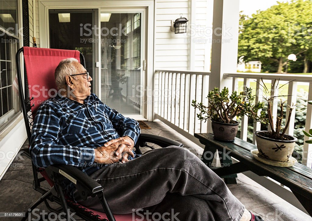 Senior Adult Elderly Man Relaxing On Front Porch stock photo
