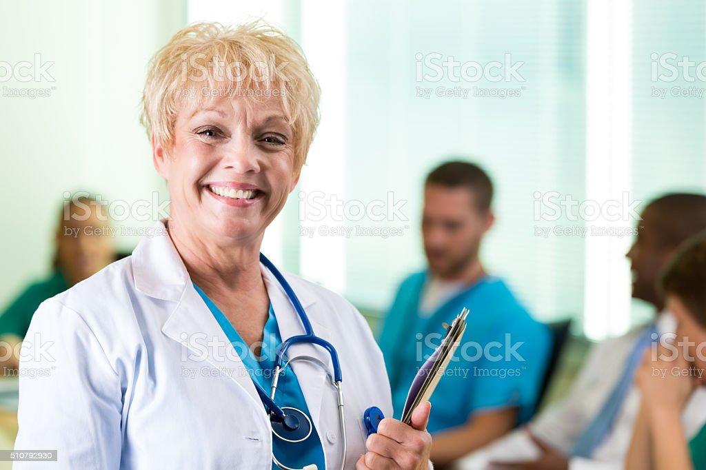 Senior adult female doctor leads hospital staff meeting stock photo