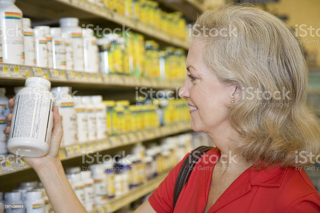 Senior Adult Female Reading Contents of Vitamin Bottle royalty-free stock photo