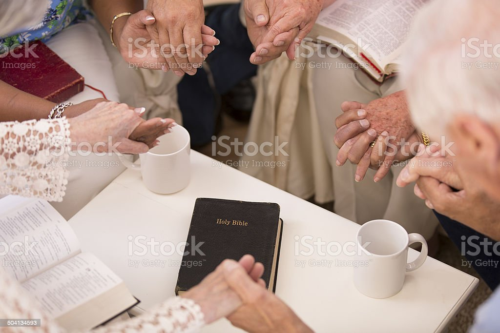Senior adult friends pray during bible study group. stock photo