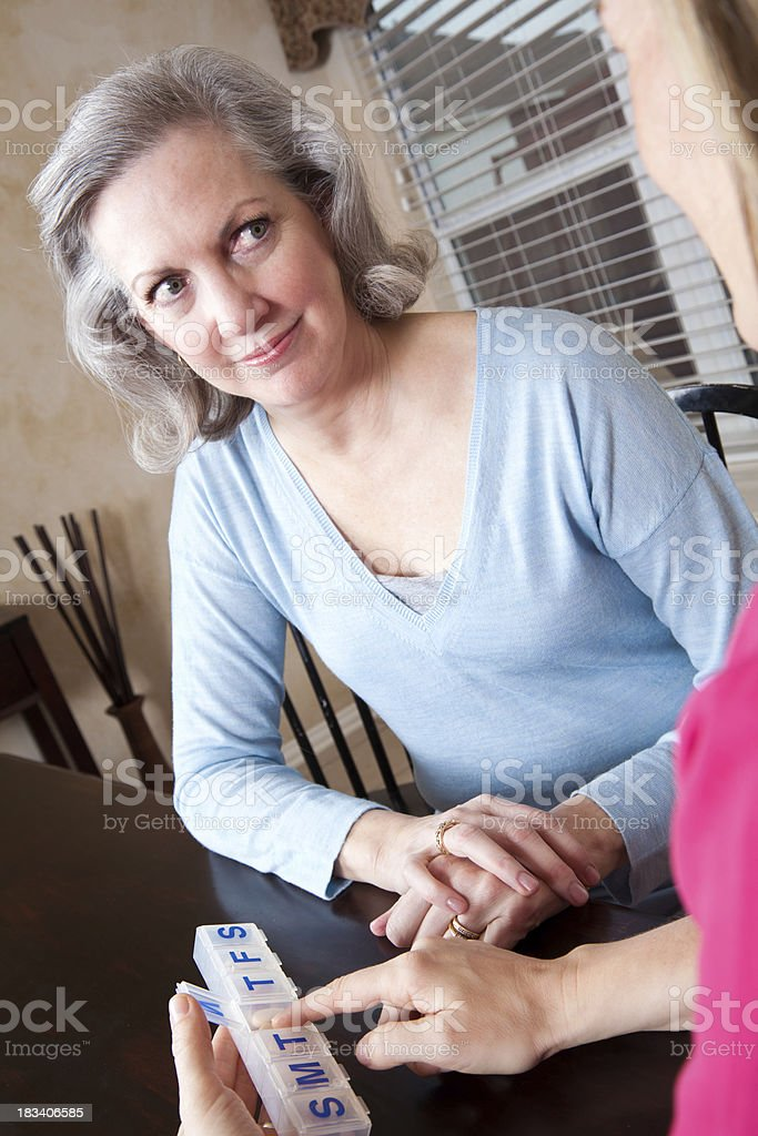 Senior Adult Getting Medication Instruction From Home Nurse royalty-free stock photo
