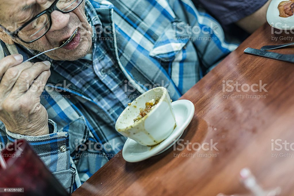 Senior Adult Grandfather Eating Lunch Soup With a Spoon stock photo