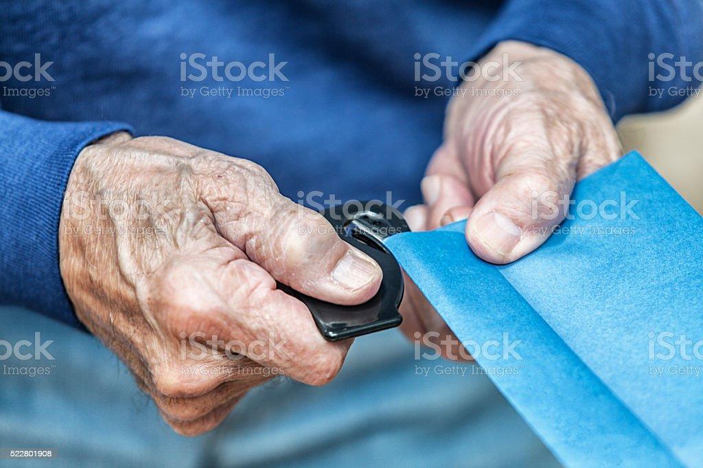 Senior Adult Hands Opening Envelope Using Letter Opener stock photo