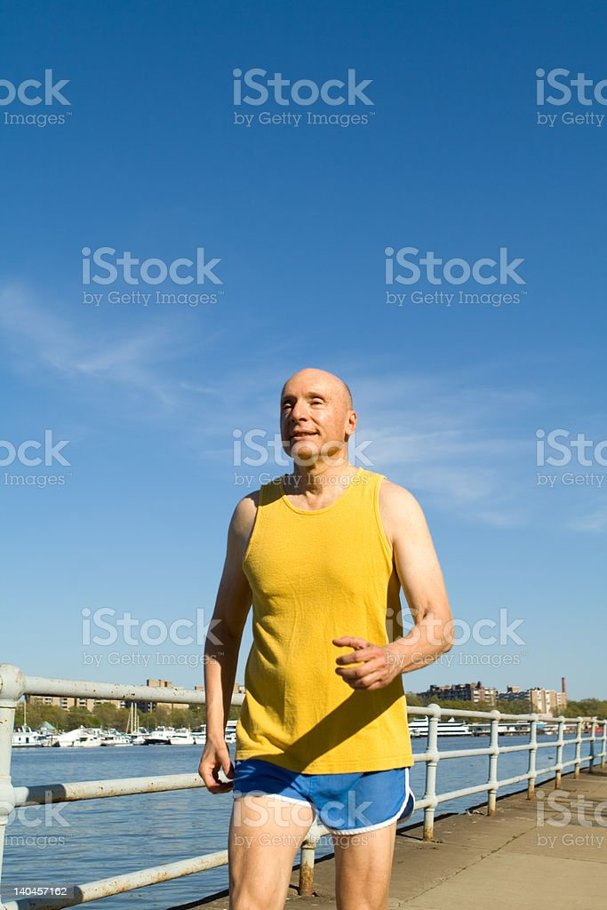 Senior Adult Jogging Along a River in Sports Gear royalty-free stock photo