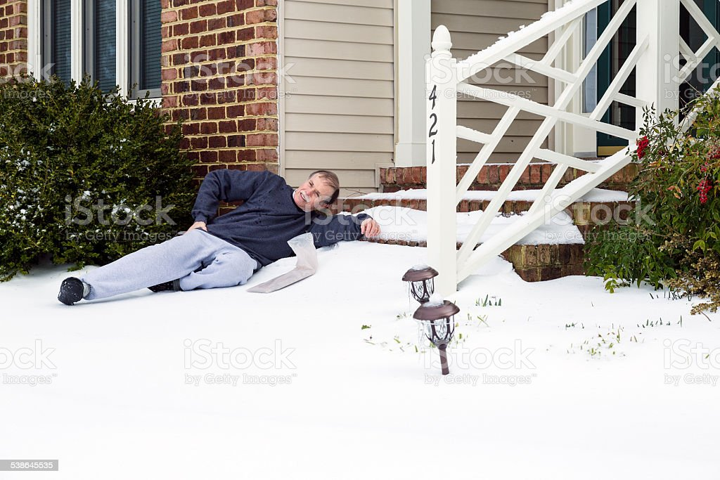 Senior adult male grimaces in pain in the snow. stock photo