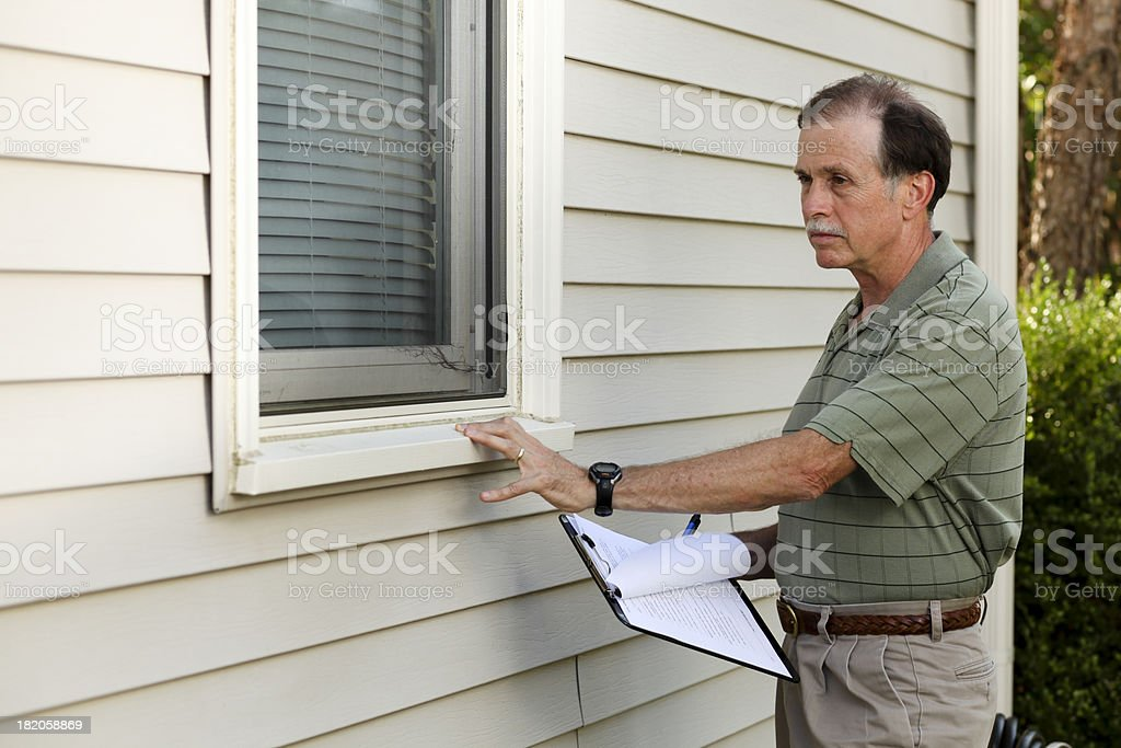 Senior adult male inspects an exterior window sill. stock photo