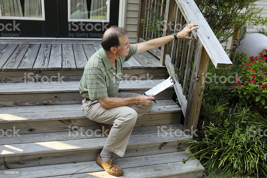 Senior adult male sitting on steps inspects a deck railing. stock photo