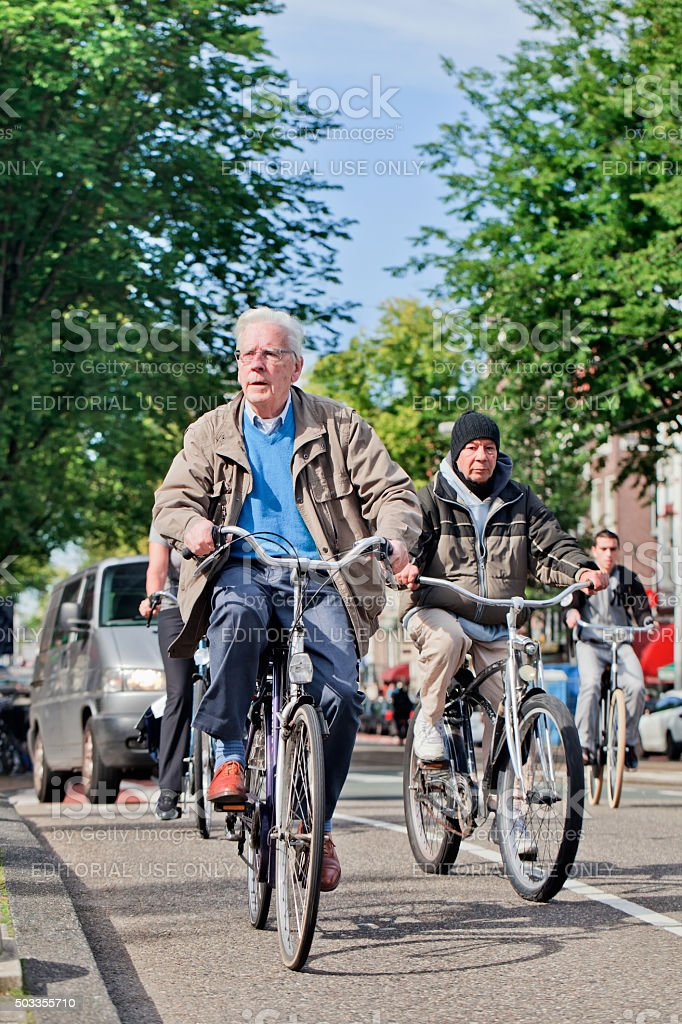 Senior adult man cycles in sunny Amsterdam city center stock photo