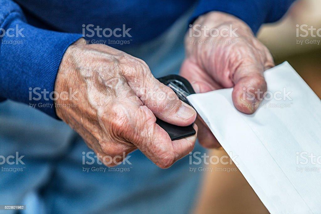 Senior Adult Man Hands Using Letter Envelope Opener stock photo