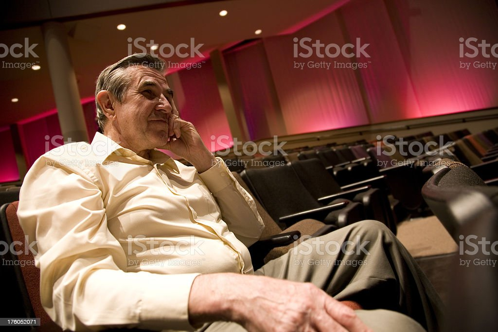 Senior Adult Man Happily Sitting in an Auditorium royalty-free stock photo