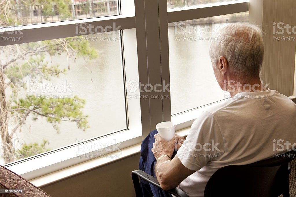 Senior adult man hospital patient waiting by window. Looking. Room. stock photo