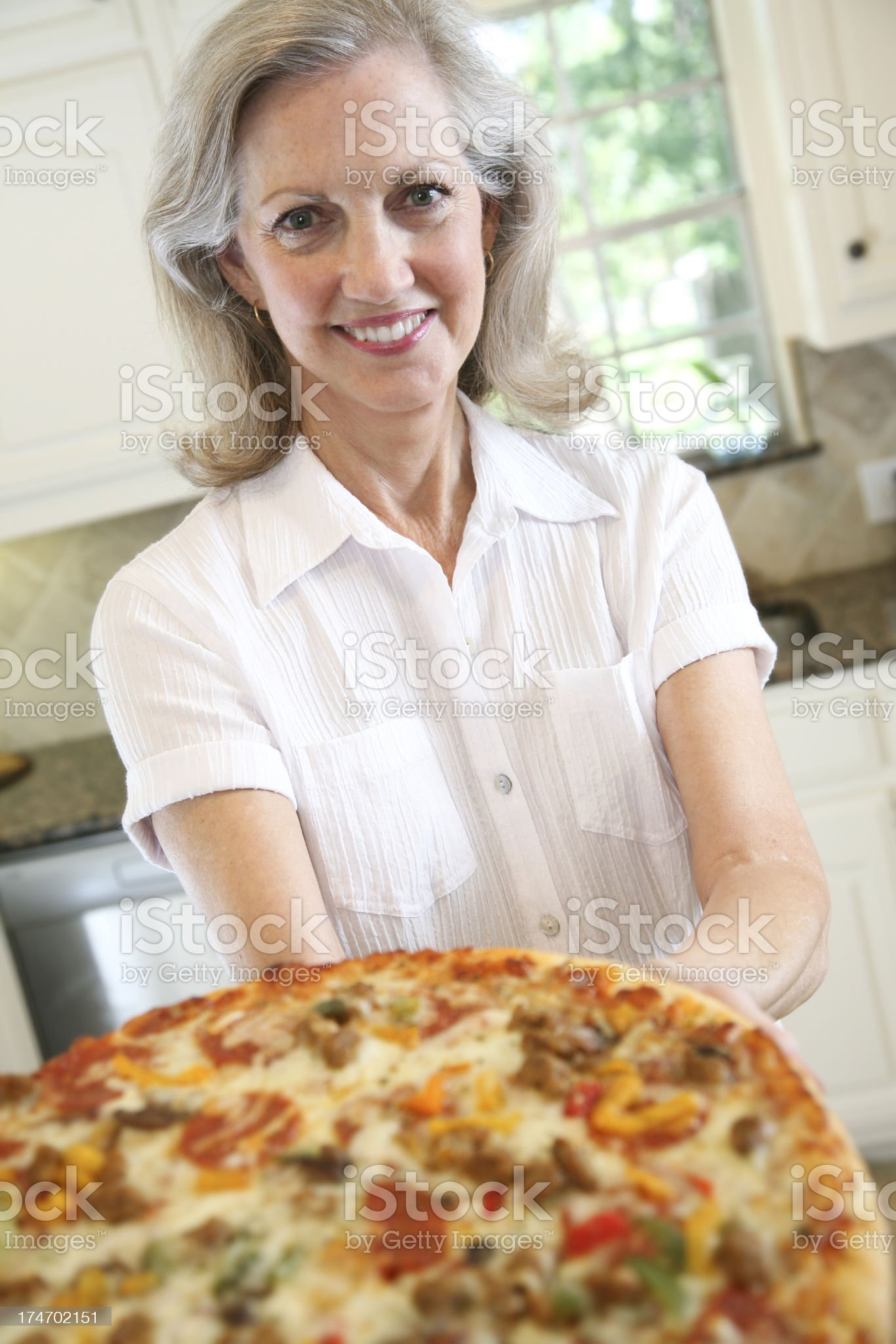 Senior Adult Offering Out a Large Supreme Pizza royalty-free stock photo