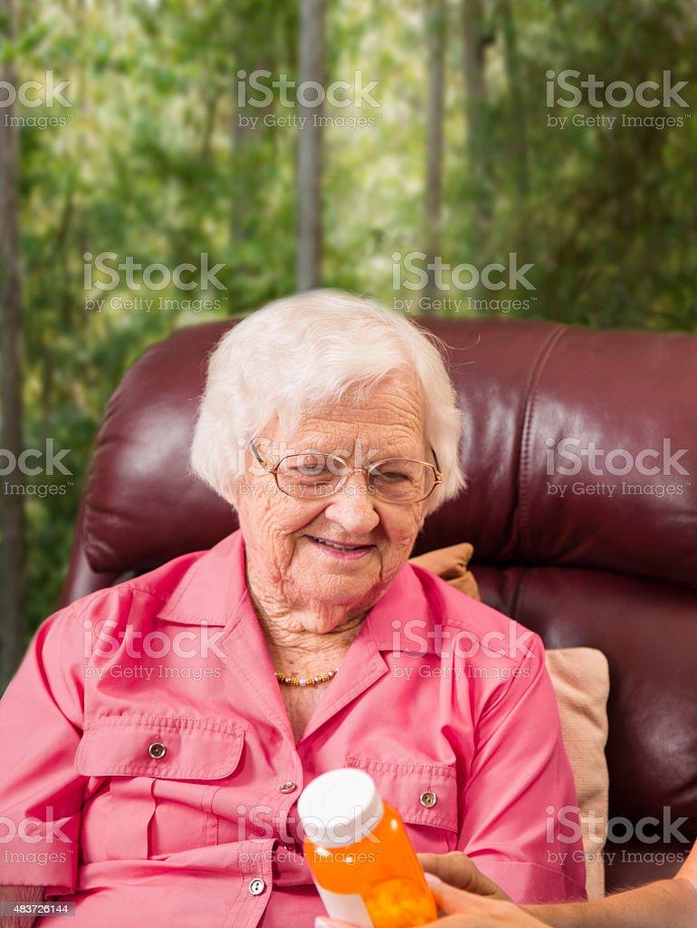 Senior adult patient reviews prescription medicine with home healthcare nurse. stock photo