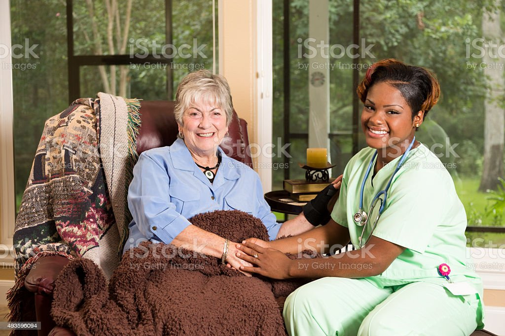 Senior adult patient with home healthcare nurse. House call. stock photo