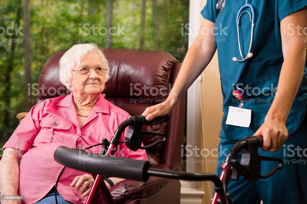 Senior adult patient with home healthcare nurse. House call. Walker. stock photo