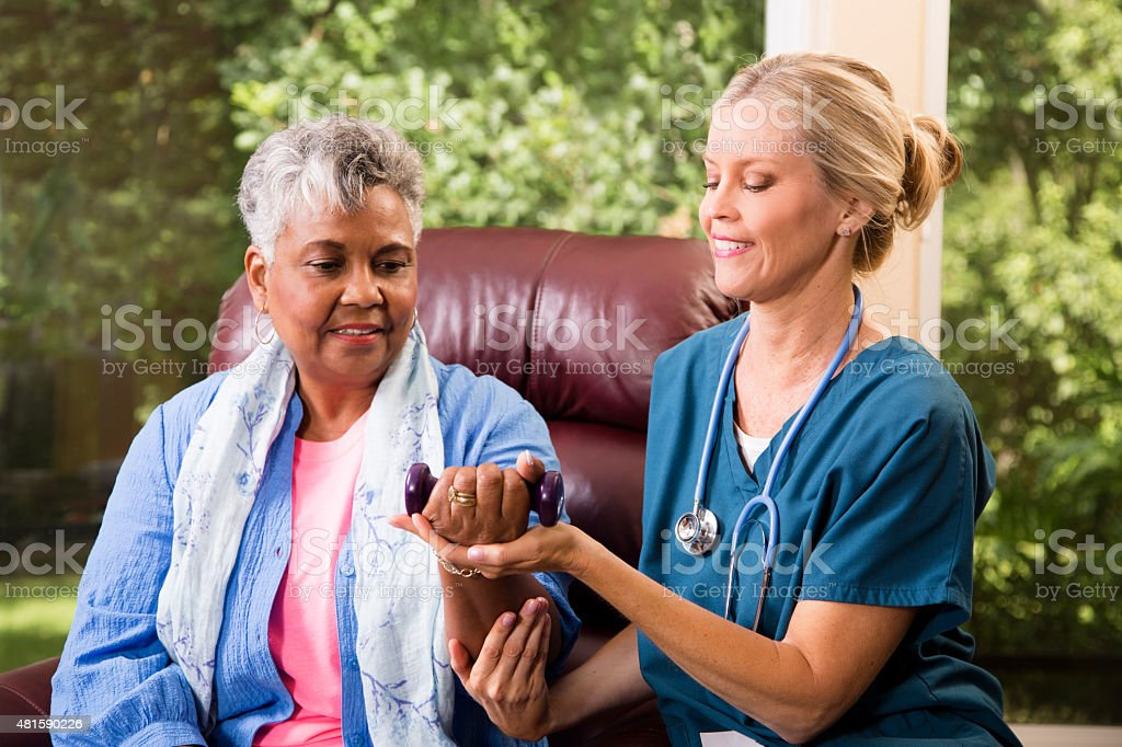 Senior adult patient with home healthcare nurse. Physical therapy. stock photo