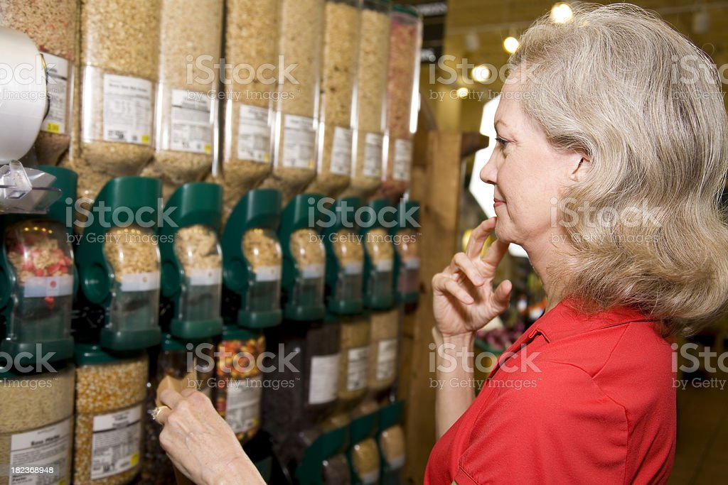 Senior Adult Shopper Making Decision on Cereal at Grocery Store stock photo