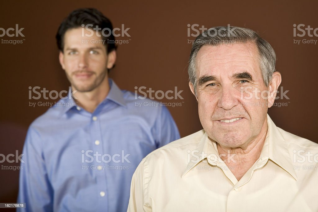 Senior Adult Standing In Front of a Younger Man royalty-free stock photo