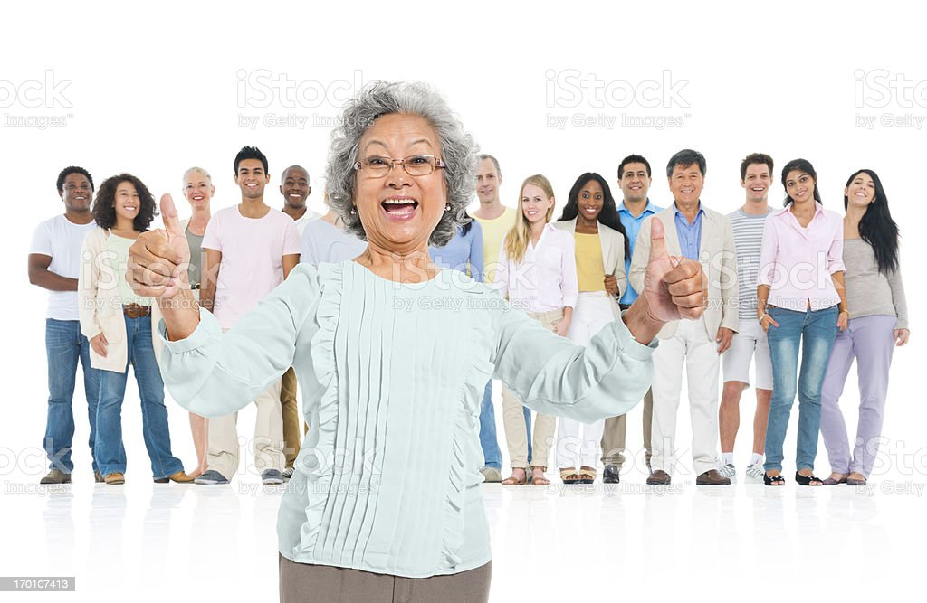 Senior adult standing out from crowd stock photo