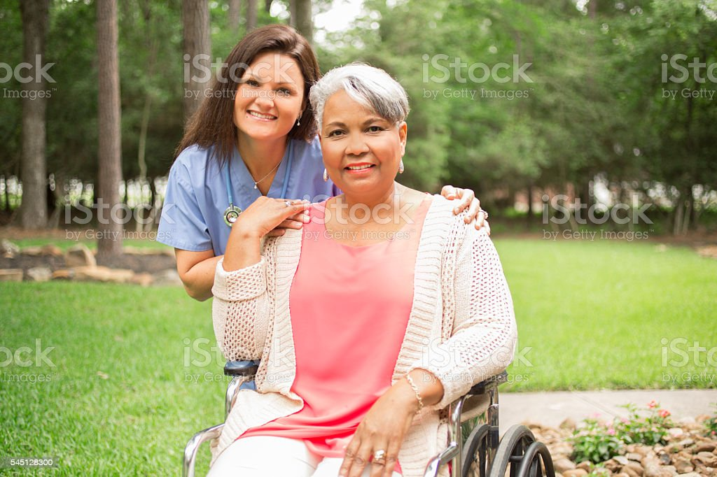 Senior adult with home healthcare nurse, caregiver outdoors.  Home, wheelchair. stock photo