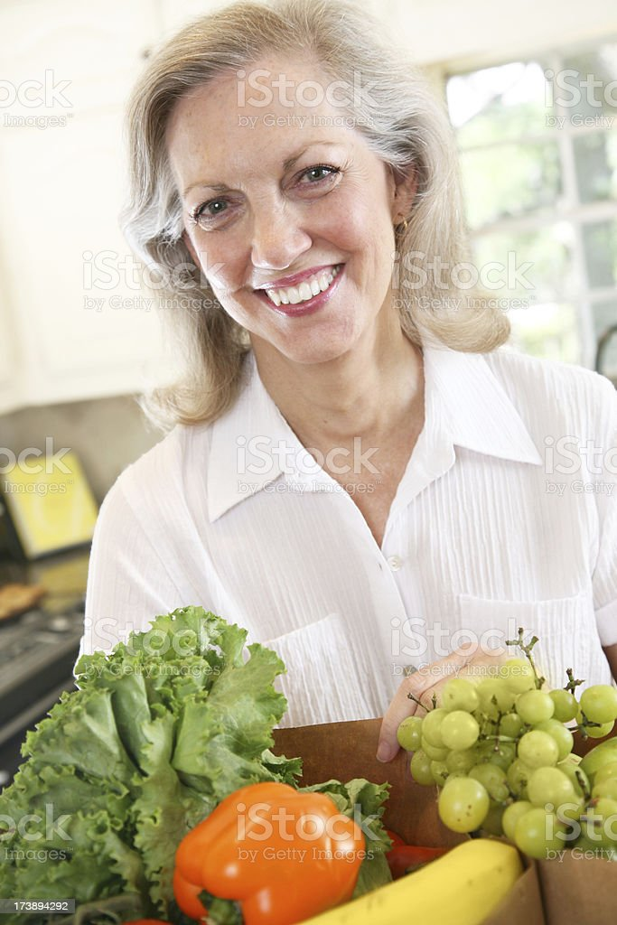 Senior Adult Woman at Home With Her Bags of Groceries royalty-free stock photo