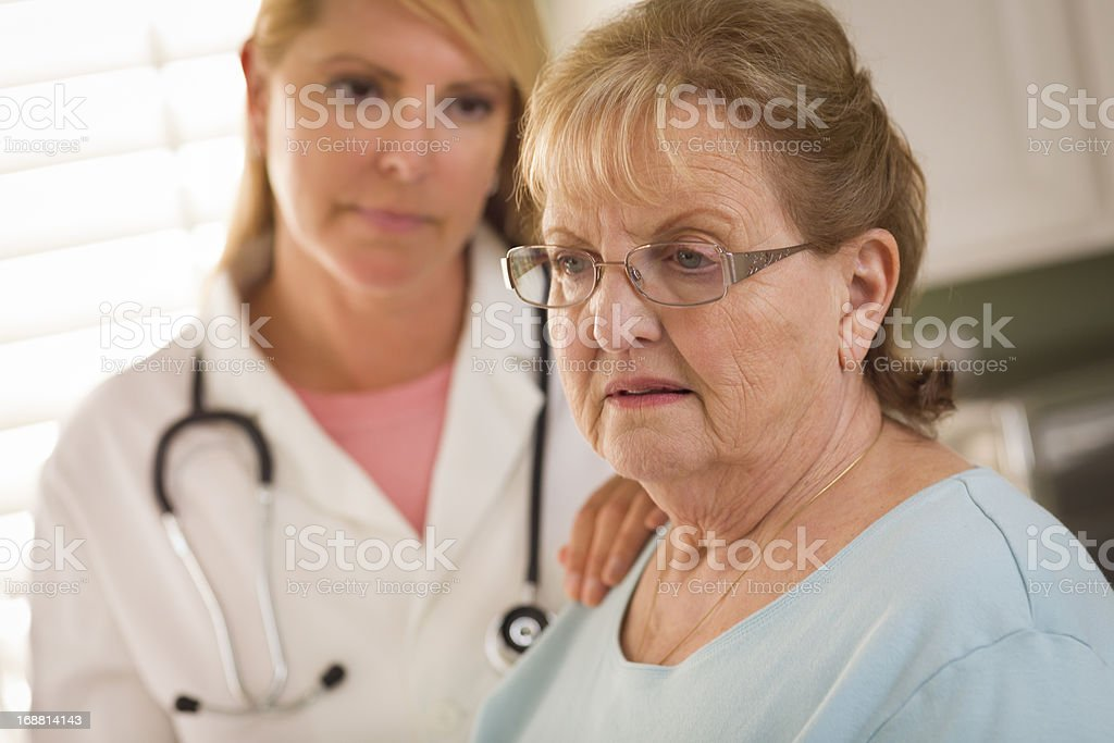 Senior Adult Woman Being Consoled by Female Doctor or Nurse royalty-free stock photo