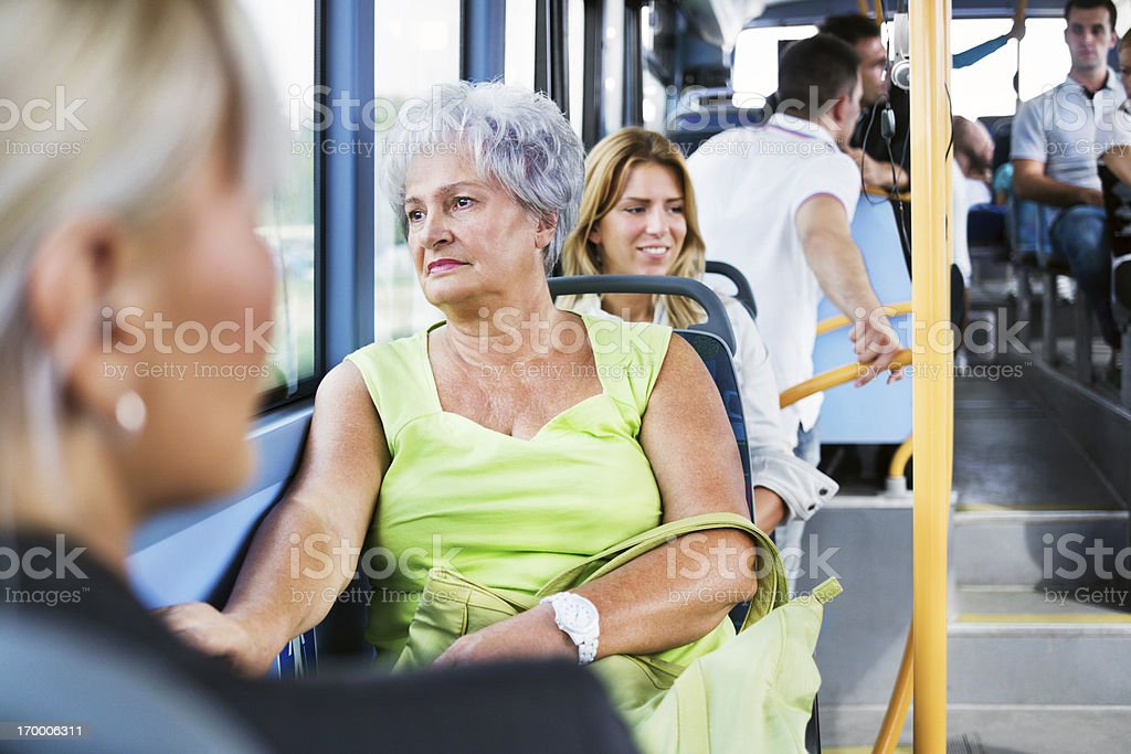 Senior adult woman commuting by bus stock photo