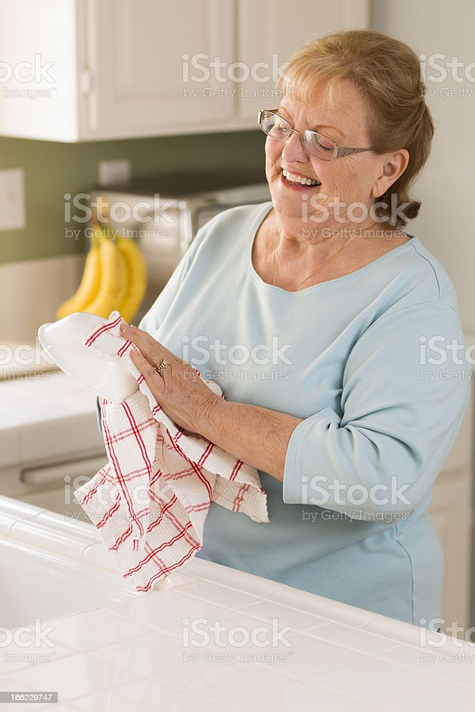 Senior Adult Woman Drying Bowl At Sink in Kitchen royalty-free stock photo
