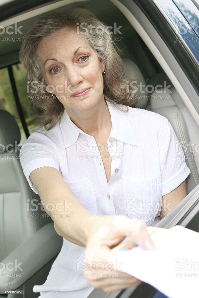 Senior Adult Woman Handing Over Insurance Papers to Authorities royalty-free stock photo