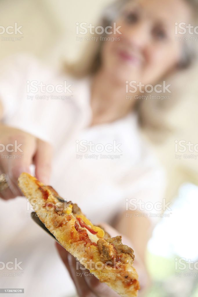 Senior Adult Woman Offering Out a Slice of Pizza royalty-free stock photo