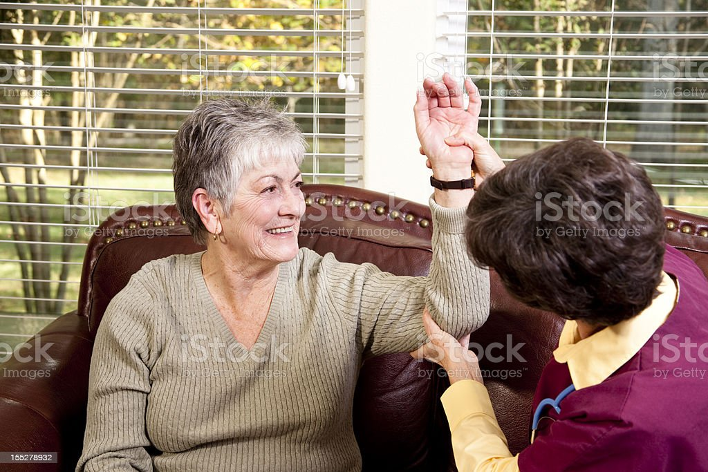 Senior adult woman receiving home physical therapy. royalty-free stock photo