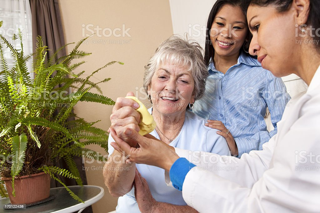 Senior adult woman receiving home physical therapy. Putty, doctor, therapist. stock photo