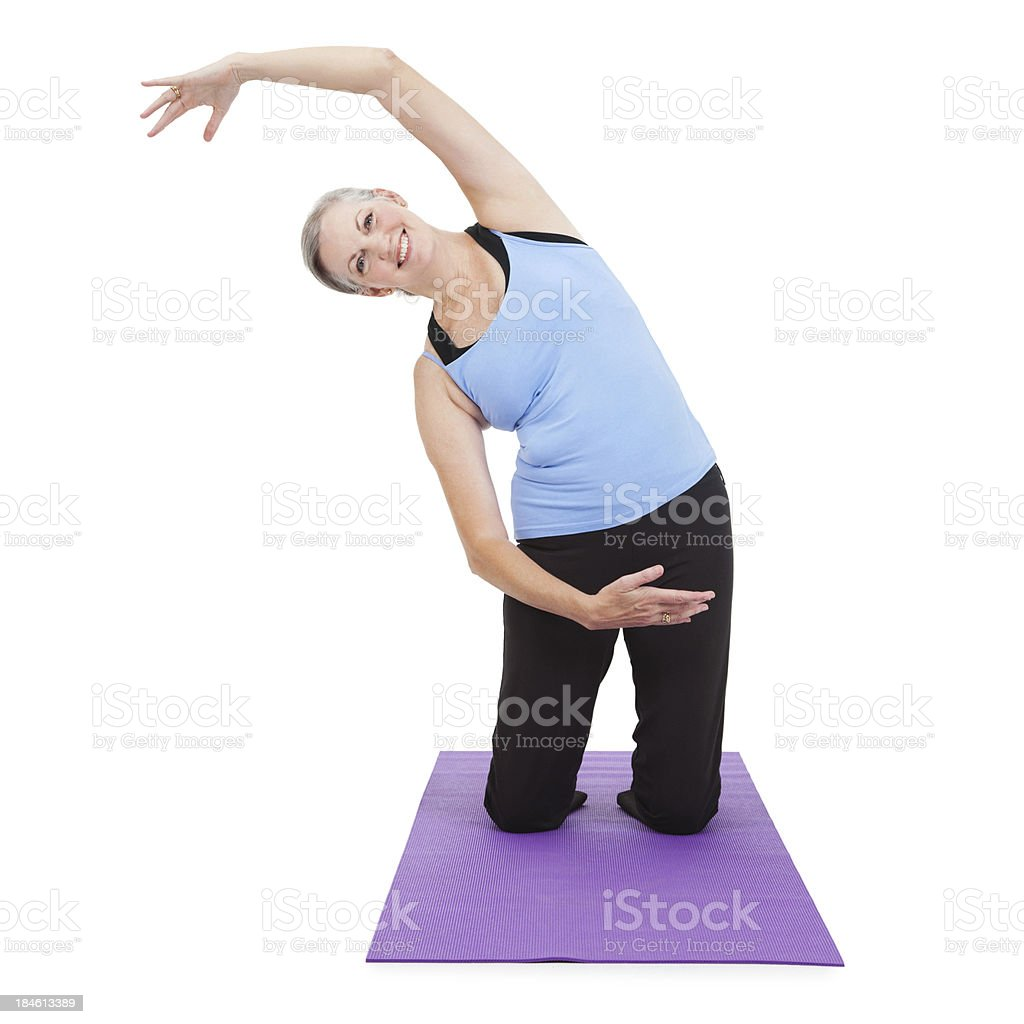 Senior adult woman stretching arm over on yoga mat royalty-free stock photo