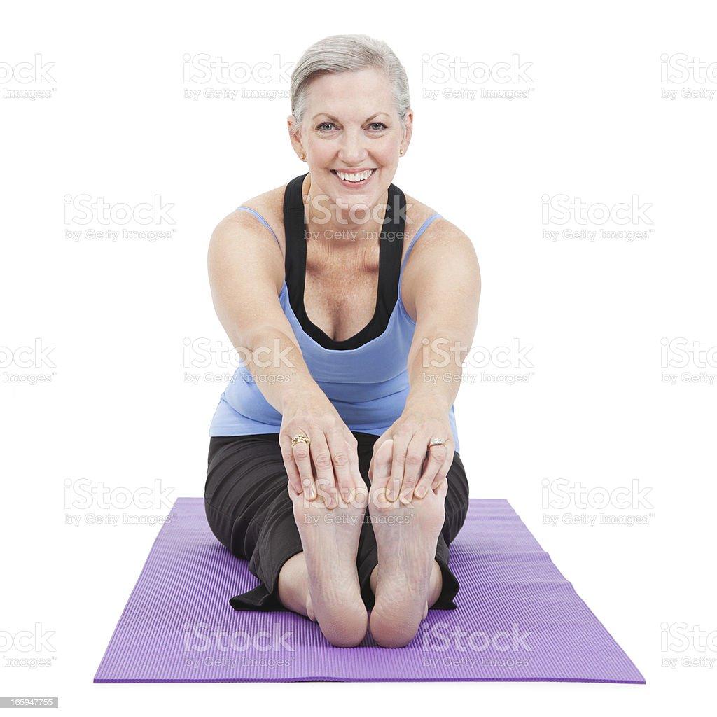 Senior adult woman stretching forward on yoga mat royalty-free stock photo