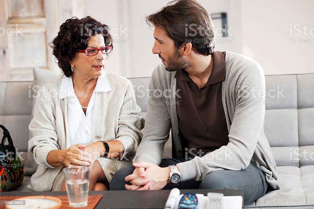 Senior adult woman talking to her son. stock photo