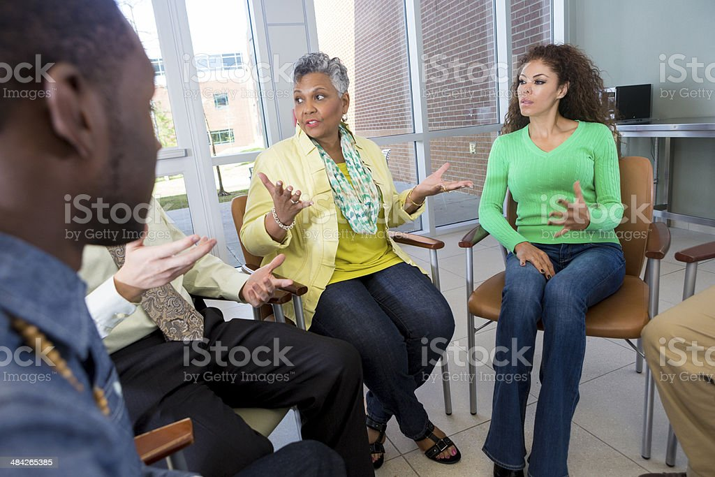 Senior adult woman talking to support or discussion group stock photo