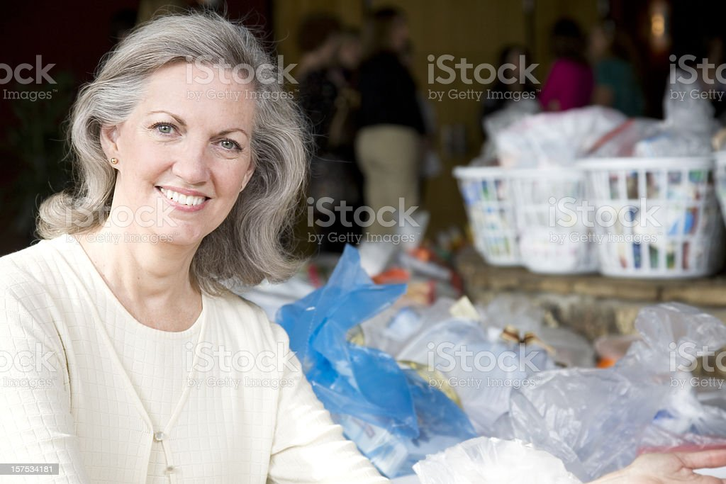 Senior Adult Woman with Baskets of Groceries at Donation Center stock photo