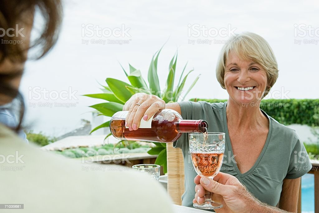 Senior adult women drinking wine stock photo