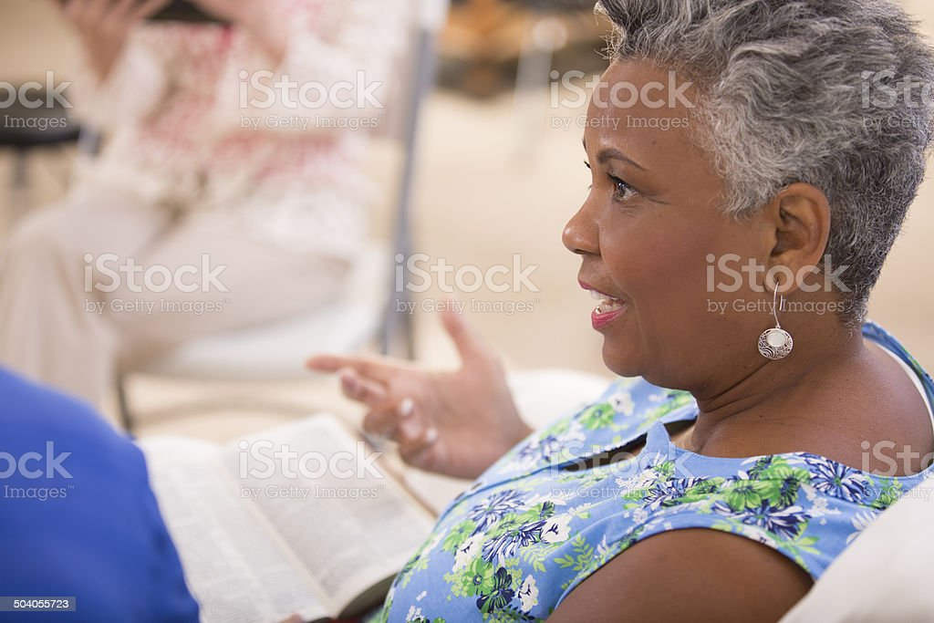 Senior adult women friends studying bible. Over shoulder view. stock photo