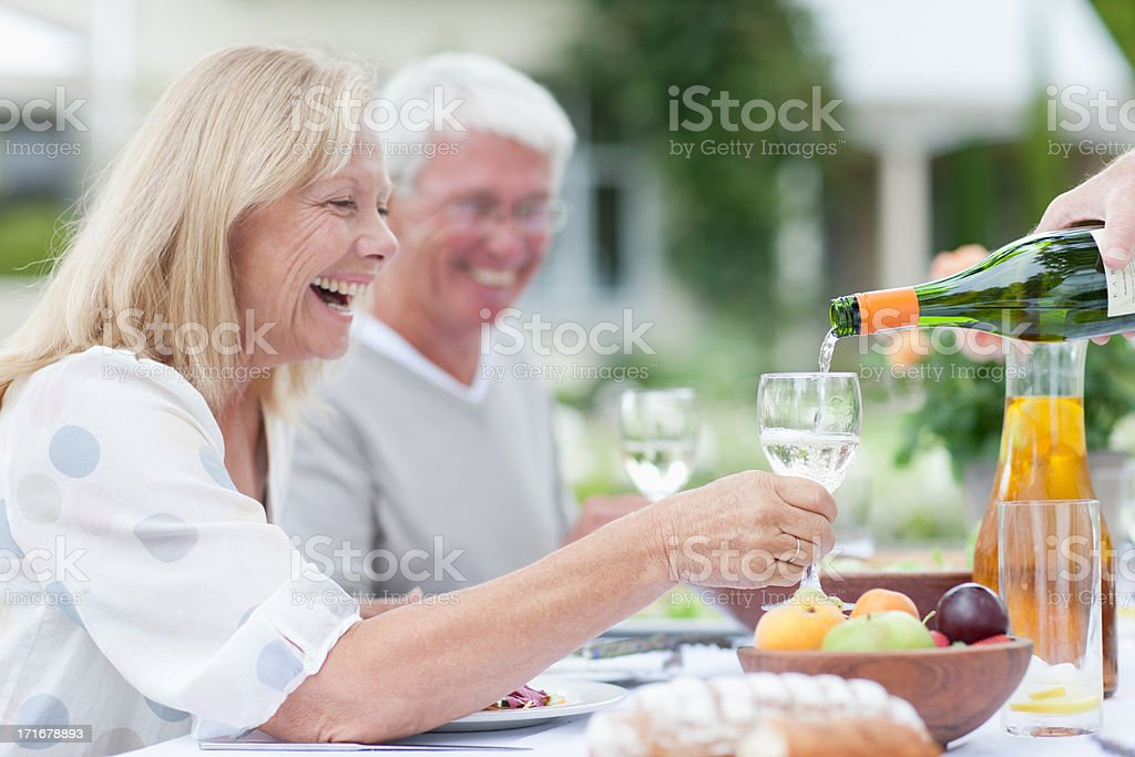 Senior adults enjoying wine at patio table stock photo
