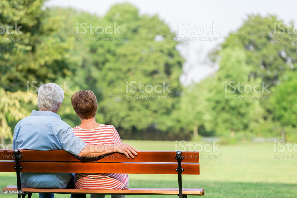 Senior adults outdoors in the park on park bench stock photo