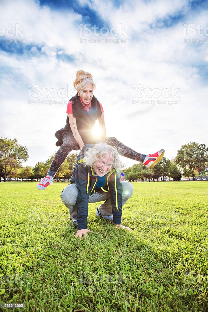 Senior adults playing leapfrog stock photo