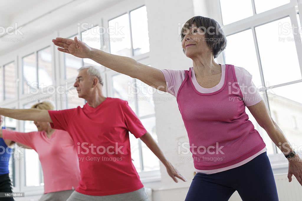 Senior adults with arms outstretched in yoga pose royalty-free stock photo