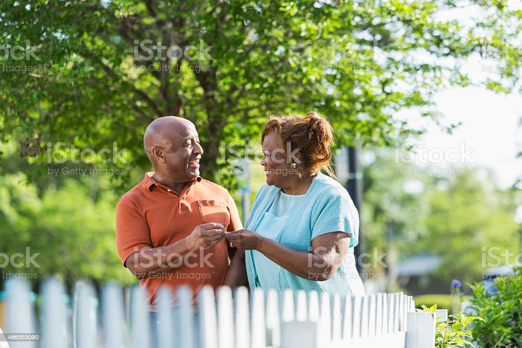Senior African American couple holding hands walking stock photo