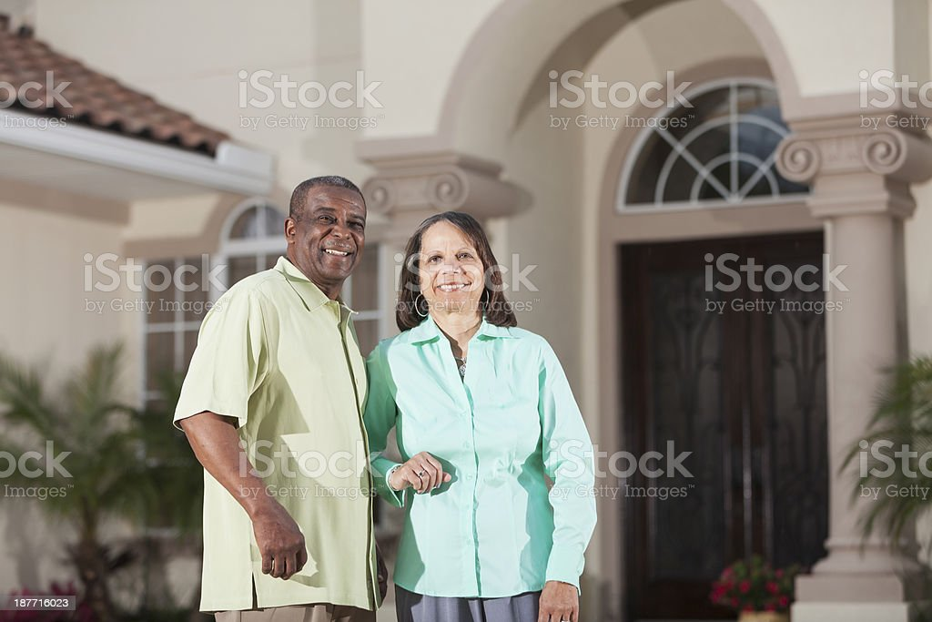 Senior African American couple in front of home stock photo