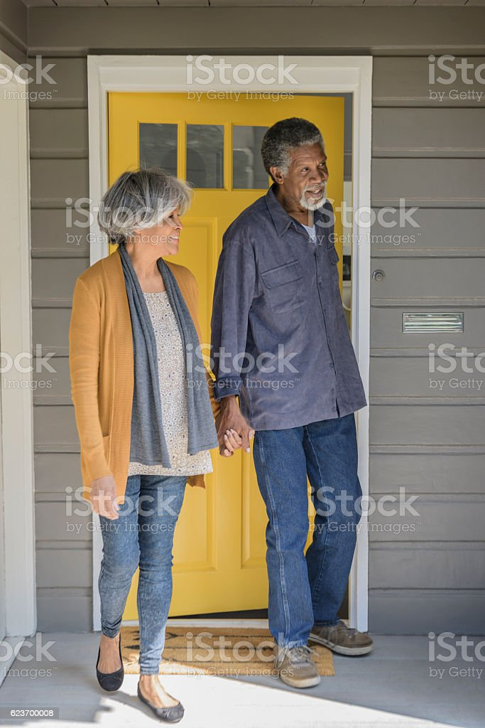 Senior African American couple leaving house and closing door stock photo